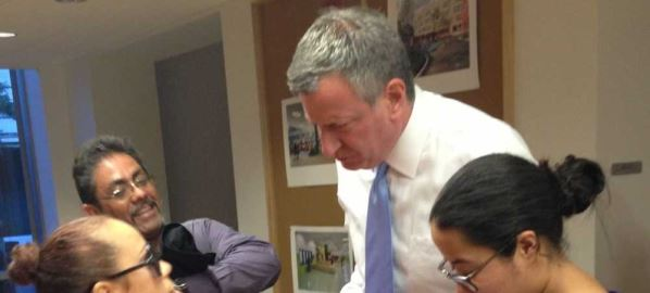 Bill de Blasio being interviewed by three reporters.