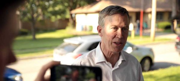 John Hickenlooper speaking with the media outside a house party in Des Mointes, Iowa.