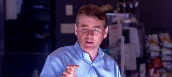 Michael Bennet speaking to patrons inside of a store.