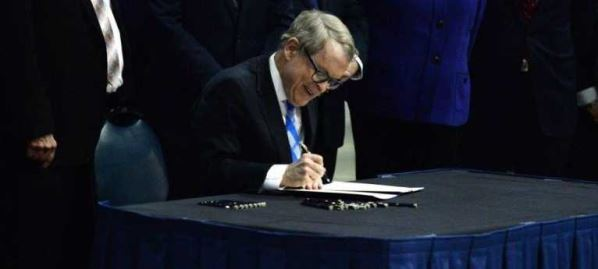 Ohio Governor Mike DeWine signs Senate Bill 7 into law at US Air Force National Museum.