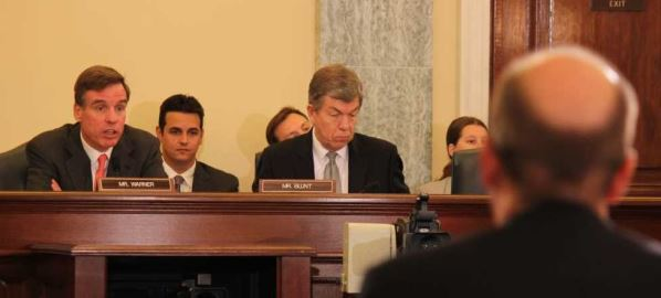 Roy Blunt and Mark Warner, question witnesses in a Surface Transportation hearing, 2013.